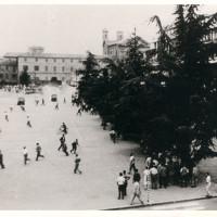 Un momento degli scontri fra forze dell'ordine e dimostranti in piazza della Vittoria il 7 luglio 1960. L'immagine è stata scattata dal balcone del teatro Ariosto. Sullo sfondo si riconoscono il palazzo dei civici musei e, a sinistra, il teatrto Romolo Valli