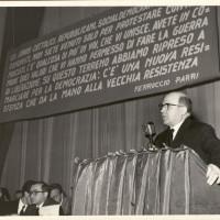 Cesare Campioli parla in occasione di una manifestazione pubblica unitaria antifascista. Sul palco si riconoscono Alcide Cervi a sinistra e Franco Boiardi con gli occhiali, verso il centro
