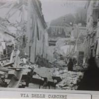 Via delle Carceri e sulla sinistra San Tommaso, vista da via San Domenico, dopo il bombardamento angloamericano dell'8 gennaio 1944. I danni alla struttura consentirono la fuga a diversi detenuti politici, incluso Alcide Cervi