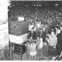 """6 settembre 1956, il pubblico assiste alla trasmissione Lascia o raddoppia? Durante la serata conclusiva dell'undicesima edizione della Festa de l'Unità di Modena. Il successo della trasmissione era tale che per assicurarsi una buona presenza di pubblico gli organizzatori della festa installarono dei televisori """"a schermo panoramico"""" per mandare in onda il gioco televisivo durante l'ultima serata.  [ISMO, AFPCMO]"""