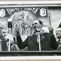 """Walter Audisio, """"Colonnello Valerio"""", parla al pubblico a Reggio Emilia nel 1947. Alla sua sinistra Didimo Ferrari """"Eros"""" e alle sue spalle un cartellone di propaganda de L'Unità"""