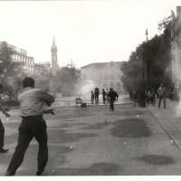 Un momento degli scontri fra forze dell'ordine e dimostranti in piazza della Vittoria il 7 luglio 1960 presso il teatro Romolo Valli, sulla sinistra. Sullo sfondo il teatro Ariosto. Successivamente parte della piazza verrà intitolata ai cinque dimostranti uccisi quel giorno dalla polizia